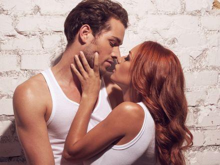 Обои Парень и девушка в белых майках целуются на фоне белой кирпичной стены