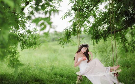 Обои Девушка азиатка в белом платье с яблоком в руке сидит на качели