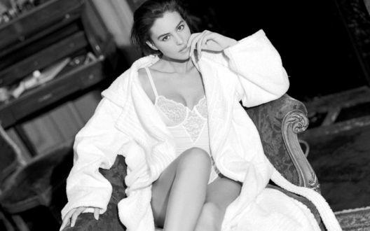 Обои Актриса Monica Bellucci в боди и белом халате сидит в кресле, поднеся руку к губам