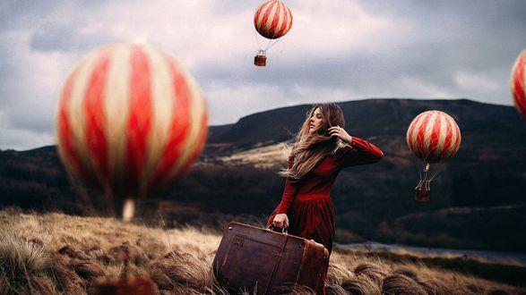 Обои Девушка с чемоданом в руке стоит на поле, над которым летят большие воздушные шары