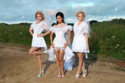 Обои Девушки из российской музыкальной группы Фабрика стоят на проселочной дороге в свадебных платьях