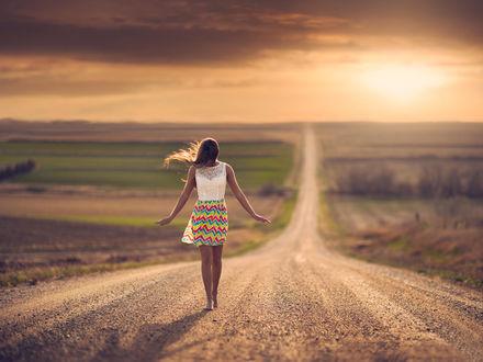 Обои Босоногая девушка на закате дня, идет по дороге среди полей