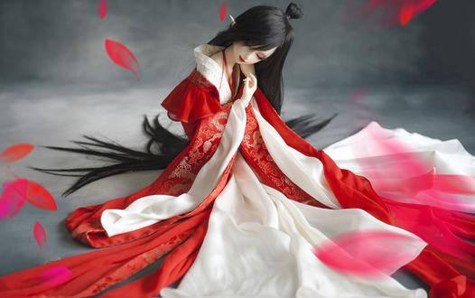 Обои Кукла-гейша в кимоно сидит на сером фоне