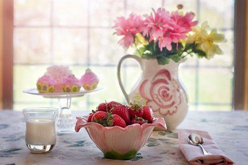 Обои Кувшин с цветами, вазочка с клубникой, стаканчик со сливками, пирожные на подставке, ложка, салфетка, окно на заднем плане, композиция на столе