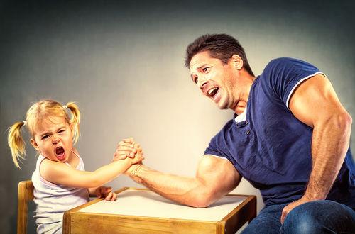 Обои Маленькая девочка и мускулистый парень борются на руках