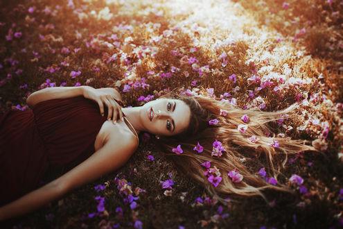Обои Девушка, волосы которой в цветах, лежит на земле, фотограф Ronny Garcia
