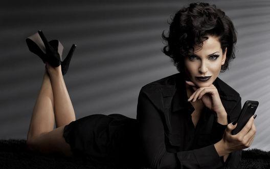 Обои Элегантная Сара Хардинг позирует, лежа на меховом ковре в черном костюме и туфлях, с телефоном в руках