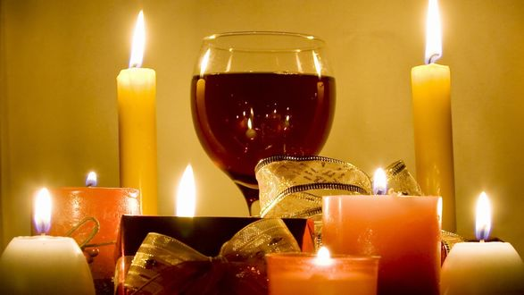 Обои Бокал вина стоит в окружении разного размера горящих свечей, рядом лежат подарки