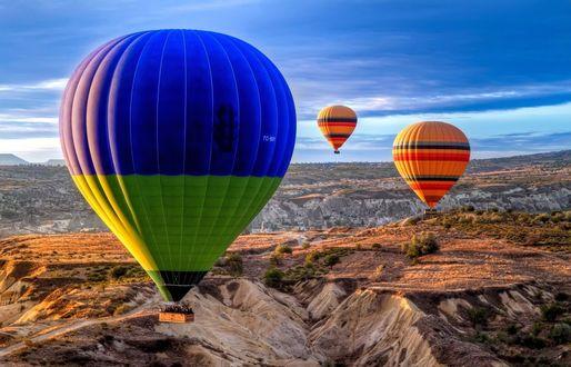 Обои Разноцветные воздушные шары в небе, над гористой местностью