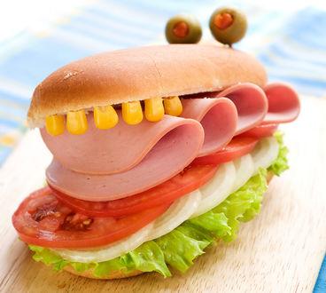 Обои Бутерброд с колбасой, помидором и луком, похожий на монстра, у которого вместо глаз зеленые оливки, а вместо зубов зерна кукурузы