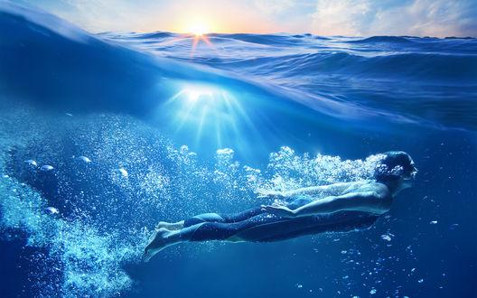 Обои Человек плывет под водой в окружении множества воздушных пузырьков