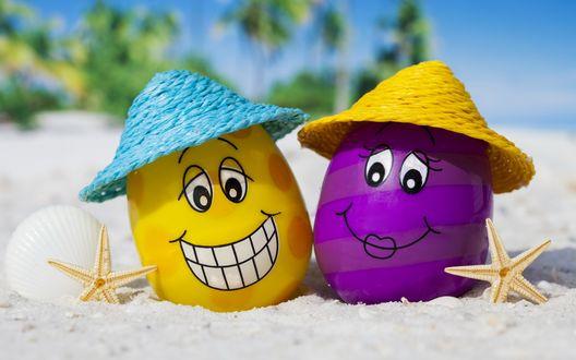 Обои Два яйца - желтое и фиолетовое, отдыхают на пляже в соломенных шляпах