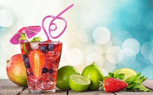 Обои Ягодный коктейль с клубникой и черникой в прозрачном стакане с трубочкой, рядом лежит клубника, манго и лайм