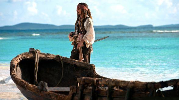 Обои Капитан Джек Воробей стоит рядом с лодкой на фоне моря / кадр из фильма Пираты Карибского моря