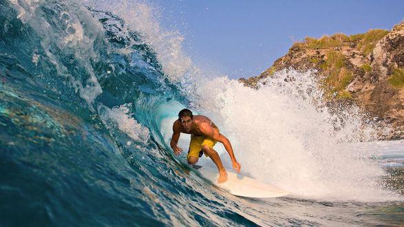 Обои Серфингист покоряет волну, пригнувшись, чтобы его не смыло с доски