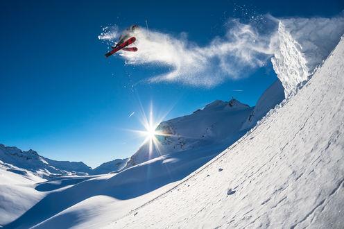 Обои Лыжник прыгает со снежного трамплина, оставляя в воздухе след из снежной пыли