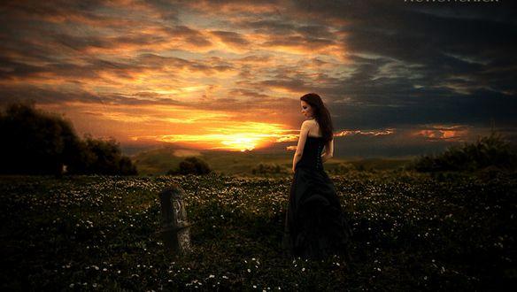 Обои Девушка в черном платье с длинными волосами стоит у надгробья на поляне на фоне вечернего заката