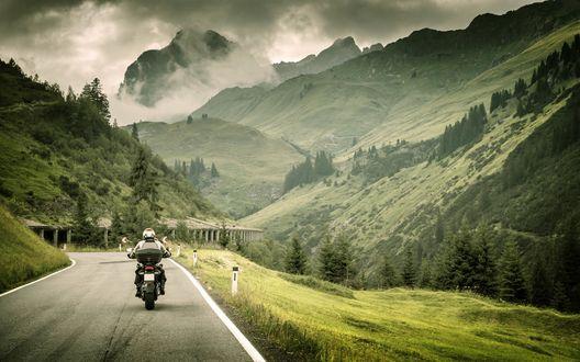 Обои Байкер едет по дороге, в окружении красивых гор