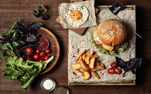 Обои На деревянном столе накрыт ланч: гамбургер, деревенская картошка, яичница, соусы, специи, помидоры черри и листья салата, базилика (room)