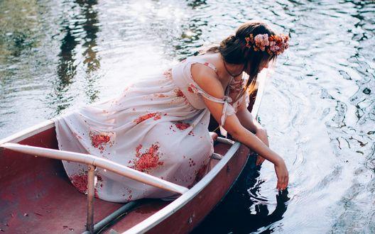 Обои Девушка в веночке трогает воду рукой, сидя в лодке