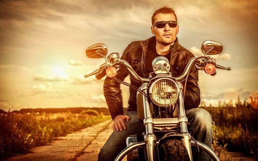 Обои Мужчина, сидя на мотоцикле, среди полей смотрит вдаль
