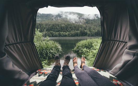 Обои Мужские и женские ноги, торчащие их большой палатки, с видом на красивый пейзаж
