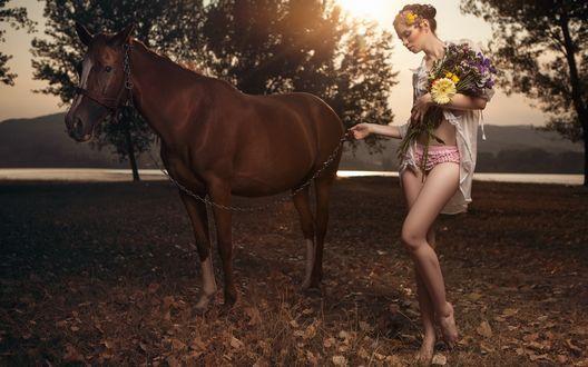 Обои Девушка в нижнем белье, распахнутой блузе с букетом цветов стоит на фоне природы, держа на цепи лошадь, by Daniel Ilinca