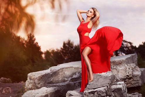 Обои Модель Momika Piwowarczyk в красном платье позирует, стоя на камнях