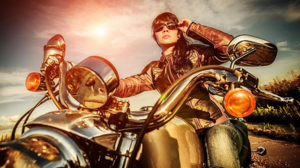 Обои Девушка в кожаной куртке и солнцезащитных очках, сидит на мотоцикле и смотрит вдаль