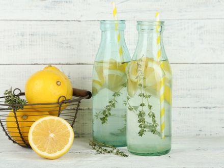 Обои Лимоны в корзинке, две бутылки с лимонной водой и трубочками