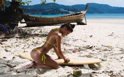 Обои Девушка с тату сидит на морском берегу, оперевшись на доску для серфинга, рядом кокос с трубочкой для коктейля, невдалеке старая лодка, модель Виктория Одинцова