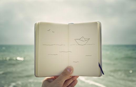 Обои Рука человека держит блокнот, на страницах которого нарисован бумажный кораблик, бегущий по волнам, на фоне моря