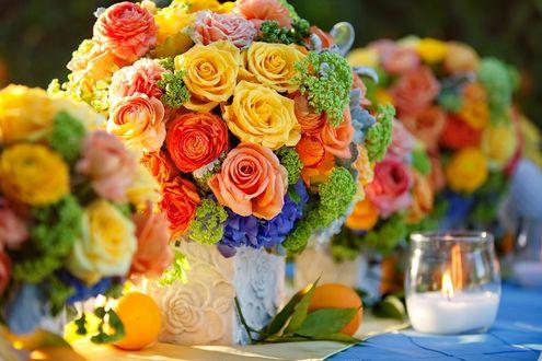 Обои Букеты из желтых, красных и розовых роз стоят на столе, рядом лимоны с листьями и зажженная свеча в стакане
