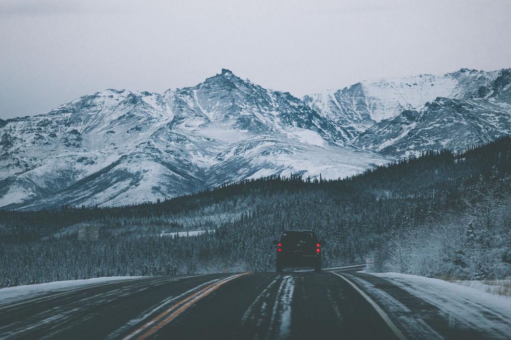 Обои для рабочего стола Автомобиль едет прямо по дороге в горы