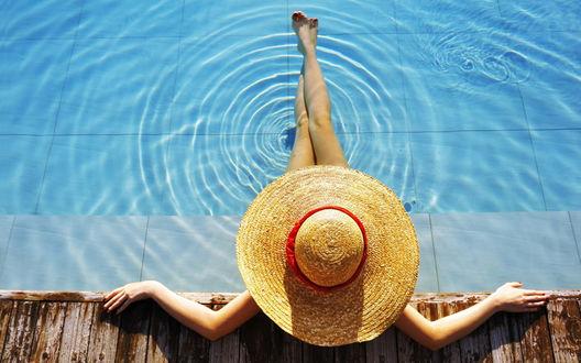 Обои Девушка в большой соломенной шляпе сидит в бассейне, вытянув ноги