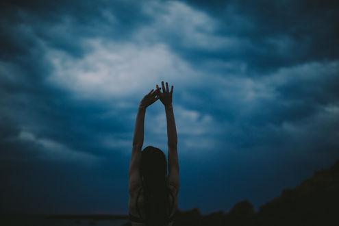 Обои Девушка с поднятыми руками стоит на фоне облачного неба, фотограф Dean Raphael