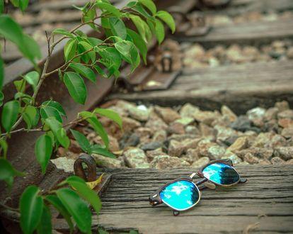 Обои Солнцезащитные очки лежат на шпалах