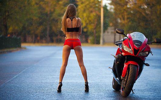 Обои Девушка в черном топе, красных шортах и туфлях, позирует у мотоцикла Honda, стоя под дождем на улице города
