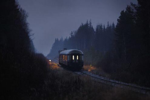 Обои Одиночный ночной вагон стоит на железной дороге