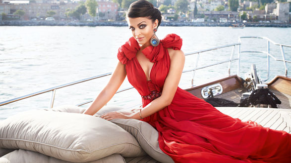 Обои Индийская актриса Aishwarya Rai в красном платье позирует, сидя на палубе корабля