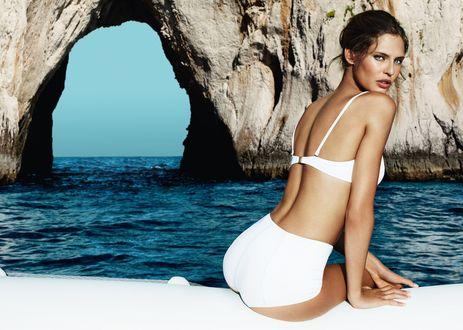 Обои Модель Bianca Balti / Бьянка Балти в белом купальнике сидит на борту яхты, оглядываясь на нас, вокруг морской пейзаж