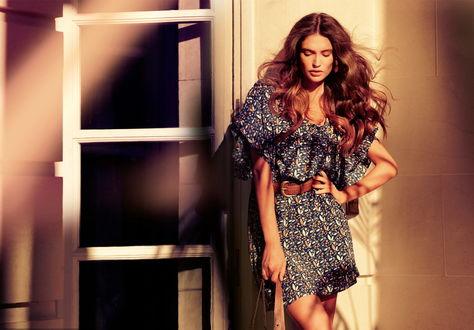 Обои Модель Bianca Balti / Бьянка Балти стоит, освещенная солнцем, у стены дома, она смотрит вниз, в руках у нее сумка