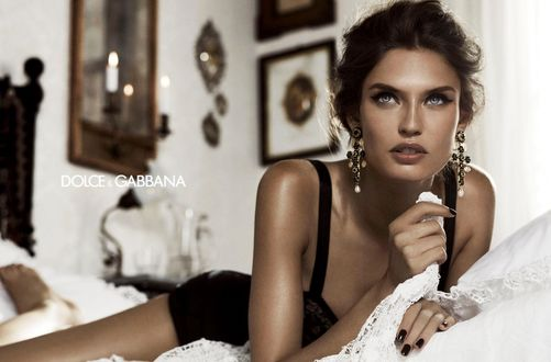 Обои Модель Bianca Balti / Бьянка Балти в нижнем белье с черным маникюром и в красивых серьгах лежит на кровати в комнате, убранной в винтажном стиле, фото для Dolce and Gabbana / Дольче и Габбана в рекламе ювелирных украшений