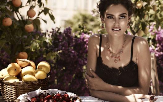 Обои Модель Bianca Balti / Бьянка Балти сидит в саду за столом, на столе корзинки с черешеней и персиками, на заднем плане фруктовые деревья и цветущие заросли, фото для Dolce and Gabbana / Дольче и Габбана в рекламе ювелирных украшений