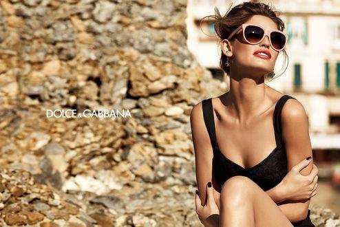 Обои Модель Bianca Balti / Бьянка Балти в солнцезащитных очках сидит на фоне города, подставив лицо солнечным лучам, фото для Dolce and Gabbana / Дольче и Габбана в рекламе очков