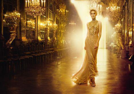 Обои Актриса Charlize Theron / Шарлиз Терон в длинном платье идет по богато убранному залу в солнечных лучах, в рекламе духов JAdore от Dior