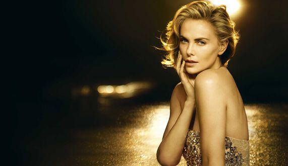 Обои Актриса Charlize Theron / Шарлиз Терон в золотистом платье поднесла руку к лицу, на черно-золотом фоне, в рекламе духов JAdore от Dior