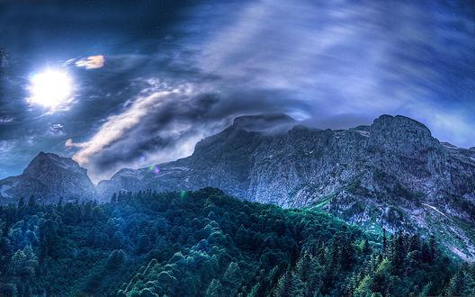 Обои Горные вершины и густой лес в свете солнца, закрытого облаками, фотограф Вадим ZUBR Малышев