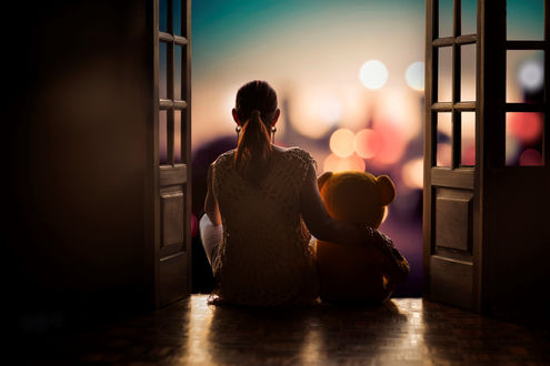 Обои Девушка с игрушечным мишкой сидят в проеме открытой двери