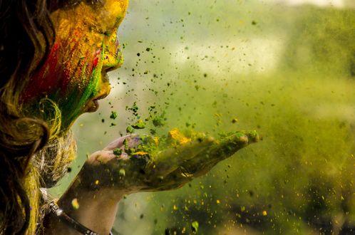 Обои Девочка, обсыпанная ярким порошком на празднике Холи, сдувает краску с ладоней